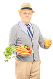 Senior gentleman holding plate with vegetables and an orange jui Stock Photo