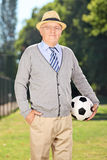 Senior gentleman holding a soccer ball in a park Royalty Free Stock Images