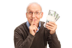 Senior gentleman holding three stacks of money Royalty Free Stock Photography