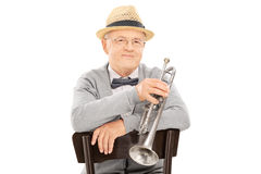 Senior gentleman holding trumpet seated on chair Stock Images