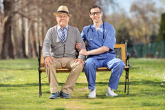 Senior gentleman and a male nurse sitting on bench Stock Photos