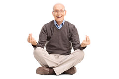 Senior gentleman meditating seated on the floor. Joyful senior gentleman meditating seated on the floor and looking at the camera isolated on white background Royalty Free Stock Image