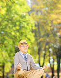 Senior gentleman meditating seated on a grass in a park Stock Image