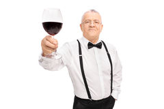 Senior gentleman proposing a toast with glass of wine. Elegant senior gentleman proposing a toast with a glass of red wine and looking at the camera isolated on Royalty Free Stock Image