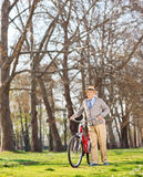 Senior gentleman pushing his bike in the park Stock Images