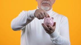 Senior gentleman putting coin in piggybank on orange background, pension fund. Stock footage stock video