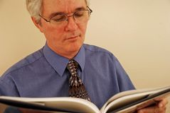 Senior Gentleman Reading. Baby-boomer man with glasses reading a book Royalty Free Stock Photo