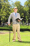 Senior gentleman reading a book and looking at camera in park Royalty Free Stock Images