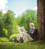 Senior gentleman reading a newspaper in park. Relaxed senior gentleman reading a newspaper seated on the grass in a park and enjoying a beautiful sunny summer Royalty Free Stock Images
