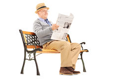 Senior gentleman reading newspaper and sitting on a bench. Senior gentleman reading newspaper and sitting on a wooden bench isolated on white background Royalty Free Stock Images