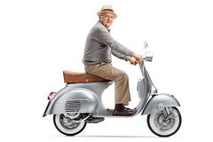 Senior gentleman riding a vintage scooter royalty free stock photography
