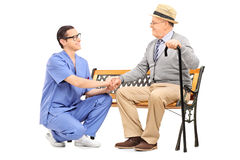 Senior gentleman seated on bench talking to male healthcare prof. Essional against white background Royalty Free Stock Images