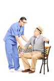 Senior gentleman seated on bench talking to male nurse Stock Photography