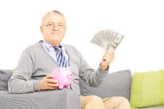 Senior gentleman seated on a sofa holding a piggy bank and dolla Stock Photos