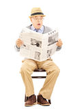 Senior gentleman in shock on a wooden chair reading a newspaper Royalty Free Stock Image