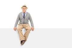 Senior gentleman sitting on a blank billboard Royalty Free Stock Images