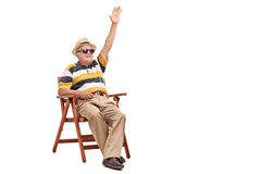 Senior gentleman sitting in a chair and waving Stock Photo