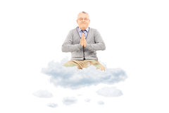 Senior gentleman sitting on clouds and meditating Royalty Free Stock Photos