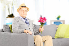 Senior gentleman sitting on a couch and holding flowers at home Stock Image