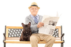 Senior gentleman sitting with his dog and reading newspaper. Senior gentleman sitting on a bench with his dog and reading newspaper isolated on white background royalty free stock photo