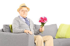 Senior gentleman sitting on a sofa and holding flowers Stock Images