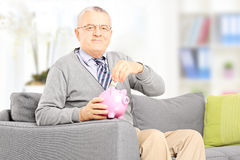 Senior gentleman sitting on sofa and putting money into piggyban Stock Photography