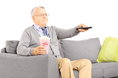 Senior gentleman sitting on a sofa and watching TV Stock Image