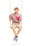 Senior gentleman sitting on swing and holding flowers Stock Photo