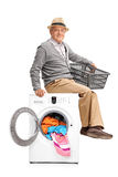 Senior gentleman sitting on a washing machine Royalty Free Stock Photo
