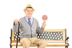 Senior gentleman sitting on a wooden bench and holding a colorful lollipop. Isolated on white background royalty free stock photo