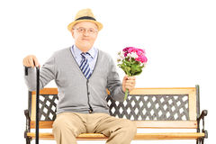 Senior gentleman sitting on a wooden bench and holding flowers Stock Image