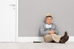 Senior gentleman sleeping seated on the floor Stock Photos