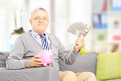 Senior gentleman on a sofa holding a piggy bank and money at hom Royalty Free Stock Photos