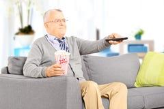 Senior gentleman on a sofa and watching TV. Senior gentleman sitting on a sofa and watching TV Stock Image