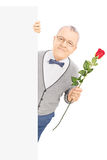 Senior gentleman standing behind blank panel and holding a red r Royalty Free Stock Photo