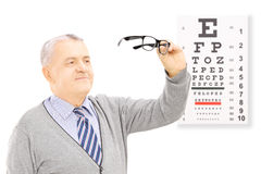 Senior gentleman standing in front of eyesight test holding a pa. Ir of glasses, isolated on white background Royalty Free Stock Photography