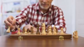 Senior gentleman training for chess competition, developing strategy, checkmate stock video footage