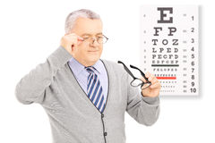 Senior gentleman trying on glasses in front of eyesight test Royalty Free Stock Photography