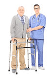 Senior gentleman with walker posing next to doctor Royalty Free Stock Images