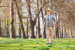 Senior gentleman walking with crutches outdoors. Senior gentleman walking with crutches in park Stock Photo