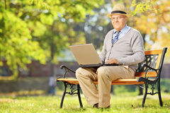 Senior gentleman working on laptop seated on bench in park Royalty Free Stock Photography