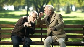 Senior gentlemen talking to his hearing impairment old friend, health problems. Stock photo stock photo