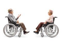 Senior gentlemen in a wheelchair talking to a senior woman in a wheelchair royalty free stock image