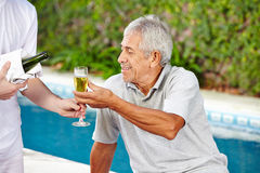 Senior getting champagne from waiter Royalty Free Stock Image