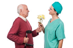Senior giving bouquet of flowers to doctor Stock Photos