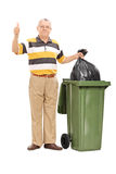 Senior giving a thumb up by a trash can Royalty Free Stock Photography