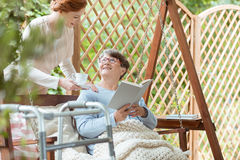 Senior with glasses reading book Stock Image