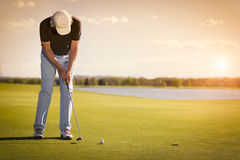 Senior golf player on green with copyspace. Male senior golf player putting on green at beautiful sunset, with empty copyspace Stock Image