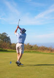 Senior golfer playing golf. Senior male golfer playing golf from the tee box on a beautiful summer day Royalty Free Stock Photo