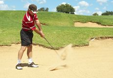 Senior golfer playing golf from sand bunker. Senior male golfer playing golf from the sand bunker on a beautiful summer day Royalty Free Stock Image